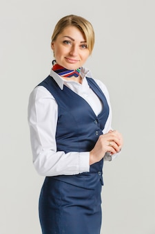 Retrato de aeromoça encantadora vestindo uniforme azul
