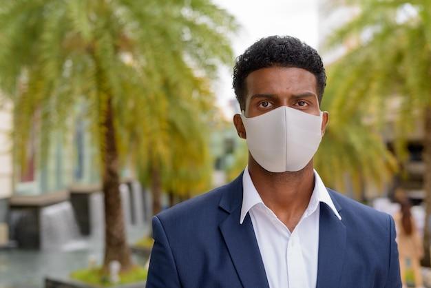 Retrato de africano retrato de um empresário africano usando máscara facial ao ar livre