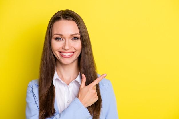 Retrato de agente de marketing positivo senhora apontar dedo indicador copyspace indicar anúncios de negócios promoção vestir terno azul isolado sobre fundo de cor brilhante