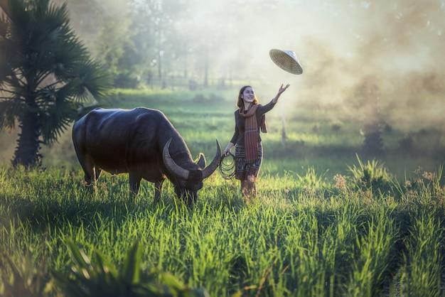 Retrato de agricultor de mulher jovem tailandês com búfalo, campo de tailândia