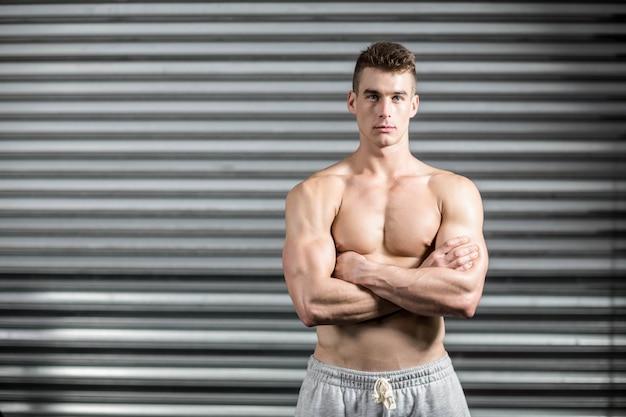 Retrato, de, ajuste, homem, com, braços cruzados, em, crossfit, ginásio