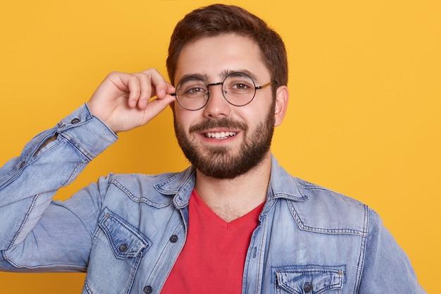 Retrato de alegre barbudo magnético feliz jovem olhando diretamente sorrindo sinceramente, tendo expressão facial agradável