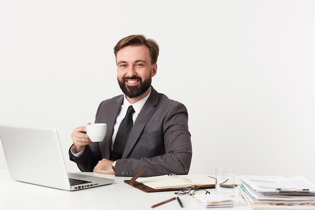 Retrato de alegre bonito jovem moreno com barba, vestindo terno cinza e gravata na parede branca, sorrindo alegremente para a frente enquanto bebe uma xícara de café