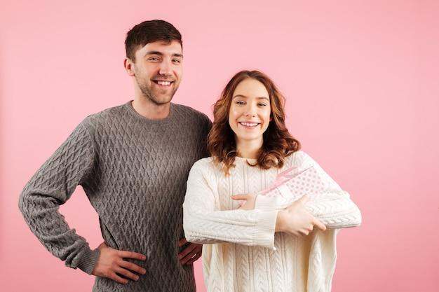 Retrato de alegre casal apaixonado, vestido de camisolas abraçando