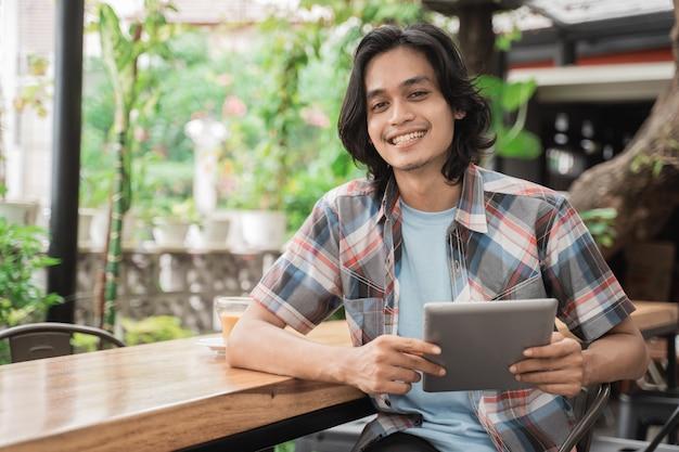 Retrato de alegre de jovem estudante asiático segurando comprimidos em um café.