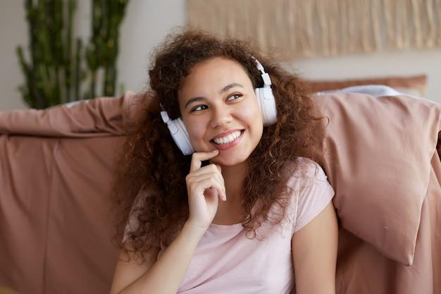 Retrato de alegre encaracolado jovem afro-americana, aproveitando o dia e desvia o olhar, amplamente sorri e ouvindo música favorita em fones de ouvido.