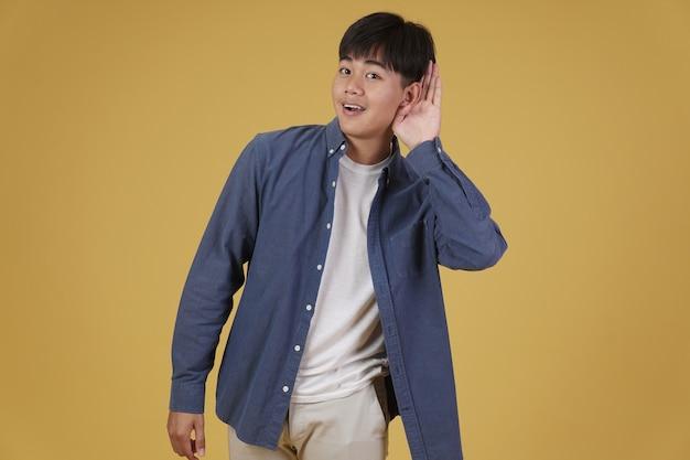 Retrato de alegre feliz regozijando-se jovem asiático vestido casualmente, colocando a mão na orelha ouvindo algo isolado