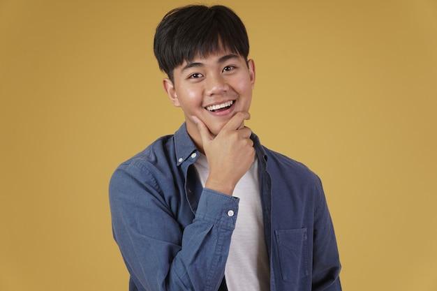 Retrato de alegre feliz regozijando-se sorridente jovem asiático vestido casualmente isolado