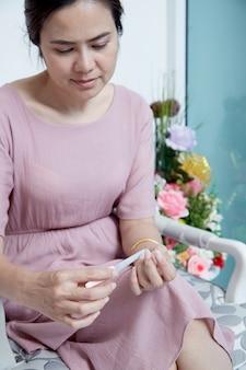 Retrato, de, alegre, feliz, sorrindo, mulher asian, com, shortinho, cabelo marrom, vestido, em, sala de estar, ela, é, fazendo, manicure, e, usando, arquivo prego