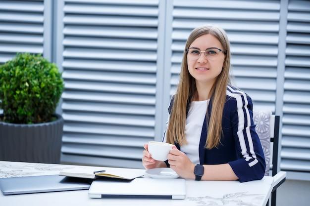 Retrato de alegre gerente europeu feminino tomando café da manhã na mesa no terraço do café, sorrindo, mulher freelancer sentada com laptop no restaurante bebendo café