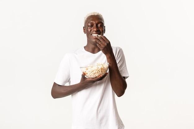 Retrato de alegre jovem atraente afro-americano, desfrutando de assistir filme e comendo pipoca, olhando para a tv sobre fundo branco.