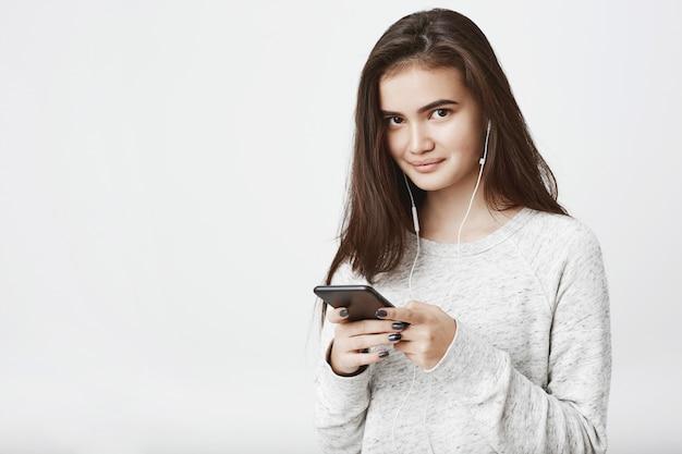 Retrato de alegre modelo europeu bonito, com longos cabelos castanhos, segurando o smartphone enquanto sorrindo amplamente e ouvindo música