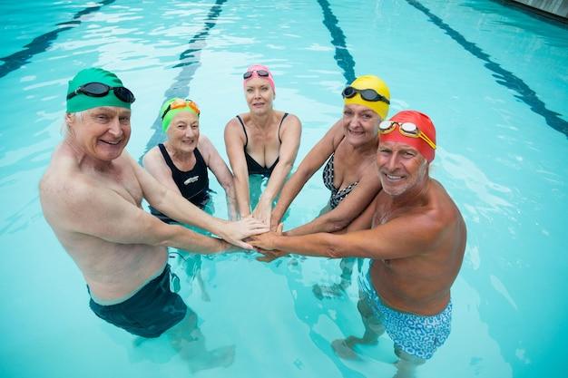 Retrato de alegre nadador sênior empilhando as mãos na piscina