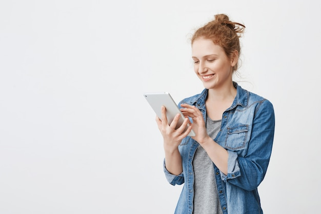 Retrato de alegre ruiva atraente estudante caucasiano com cabelo penteado em coque, digitando ou navegando em tablet