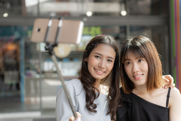 Retrato de alegres duas namoradas sorridentes fazendo um selfie em shopping center.