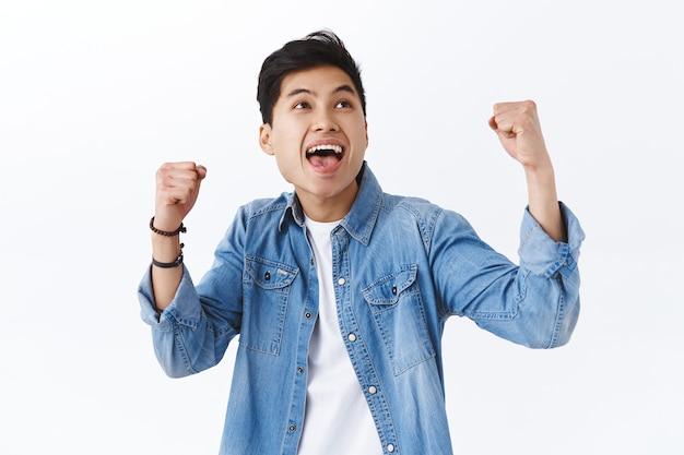 Retrato de alegria, sorrindo, feliz homem asiático levanta as mãos, vencendo, torcendo pelo time de esporte, assistindo jogo intenso, triunfando sobre a vitória