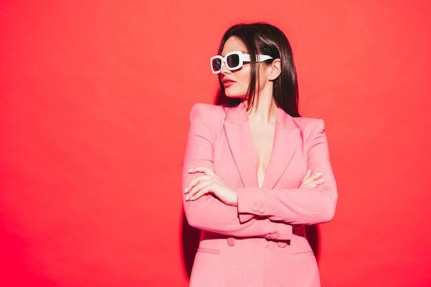 Retrato de alta moda de uma jovem morena linda usando um belo terno rosa de verão