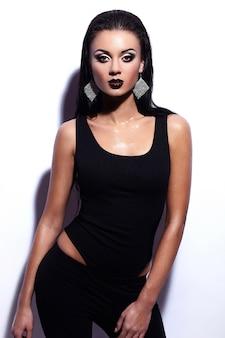 Retrato de alta moda look.glamor do modelo sexy elegante caucasiano mulher jovem e bonita em roupas pretas, posando perto da parede