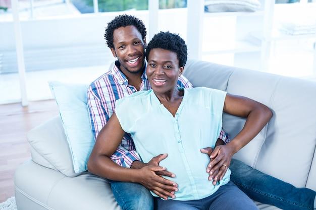 Retrato de alto ângulo de casal feliz relaxando no sofá em casa