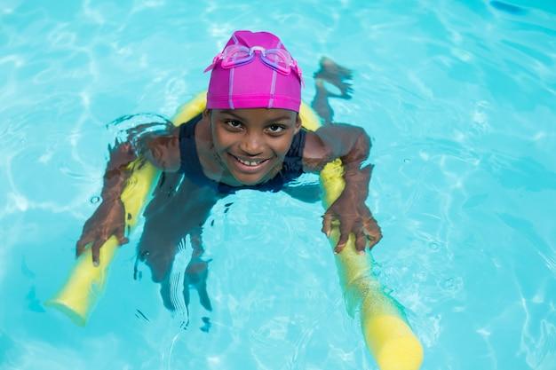 Retrato de alto ângulo de menina nadando com macarrão de piscina