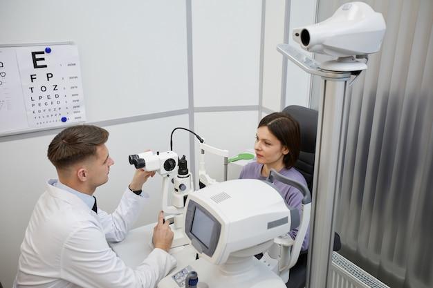 Retrato de alto ângulo de oftalmologista usando refratômetro oftálmico durante a consulta