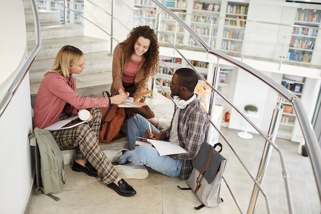 Retrato de alto ângulo de três alunos sentados em escadas na faculdade e conversando enquanto fazem o dever de casa,