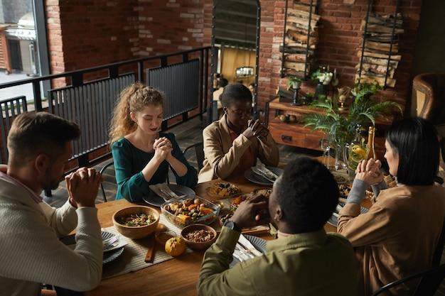 Retrato de alto ângulo de um grupo multiétnico de jovens elegantes orando de olhos fechados enquanto estão sentados à mesa de jantar durante a celebração do dia de ação de graças.