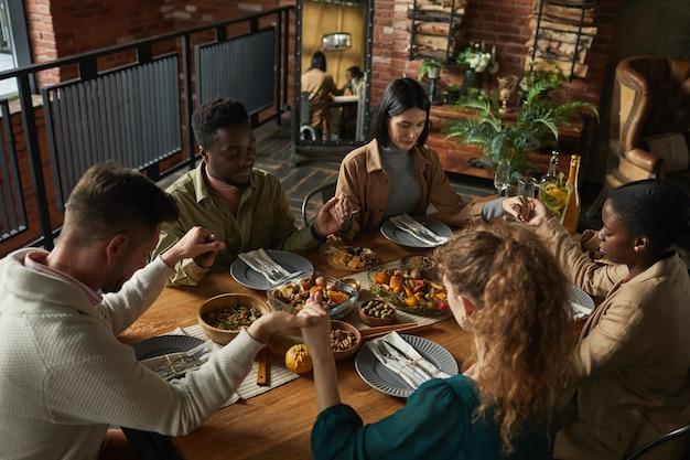 Retrato de alto ângulo de um grupo multiétnico de jovens elegantes orando e de mãos dadas enquanto estão sentados à mesa de jantar durante a celebração do dia de ação de graças.