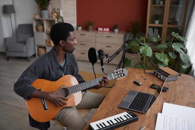Retrato de alto ângulo de um jovem afro-americano tocando violão e cantando ao microfone em um estúdio de gravação caseiro, copie o espaço