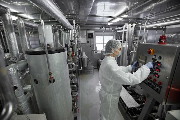 Retrato de alto ângulo de uma jovem trabalhadora operando unidades de máquina na fábrica de produção de alimentos limpos, copie o espaço