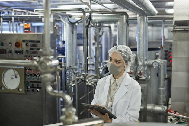 Retrato de alto ângulo de uma jovem usando máscara e segurando um tablet digital durante a inspeção de controle de qualidade na fábrica de alimentos, copie o espaço