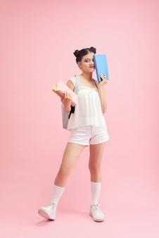 Retrato de aluna com mochila e livros sobre fundo rosa