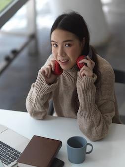 Retrato de aluna relaxando com fone de ouvido no espaço de trabalho
