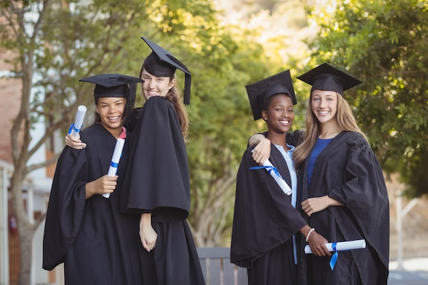 Retrato de alunos de pós-graduação em pé com a rolagem de grau no campus