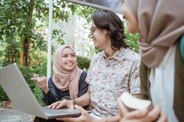 Retrato de alunos discutindo junto com o laptop no pátio do campus.