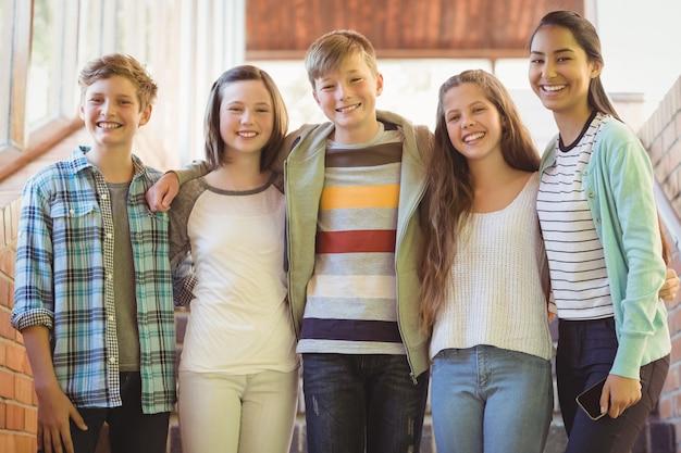 Retrato de alunos felizes em pé e com os braços no corredor