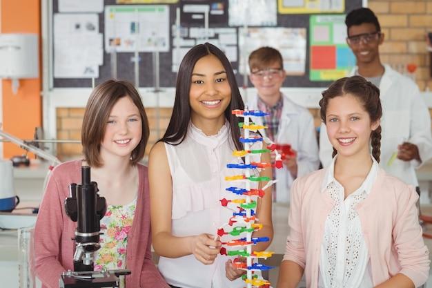 Retrato de alunos felizes experimentando modelo de molécula em laboratório