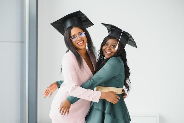 Retrato de alunos felizes segurando diplomas no dia da formatura