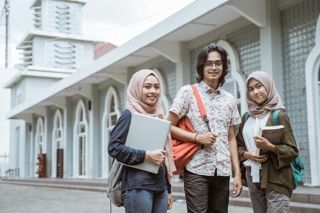 Retrato de alunos olhando para a frente no pátio do campus.
