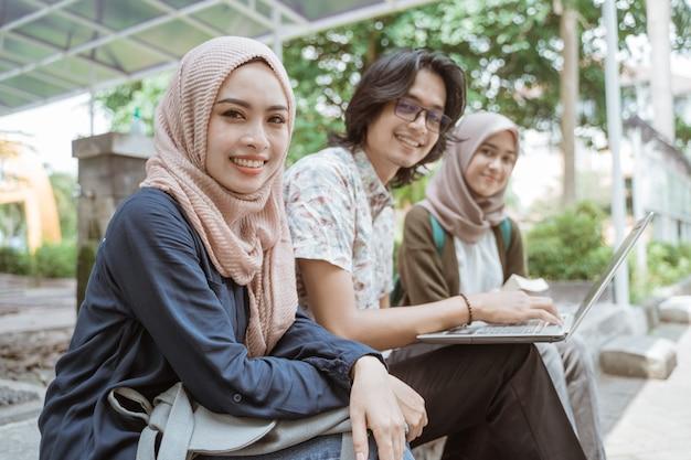 Retrato de alunos olhando para uma câmera junto com um laptop no pátio do campus