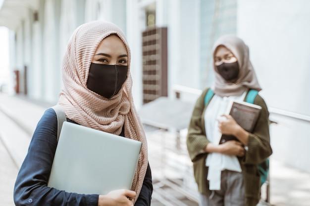 Retrato de alunos usando máscaras, olhando para a frente no pátio do campus com amigos ao fundo.