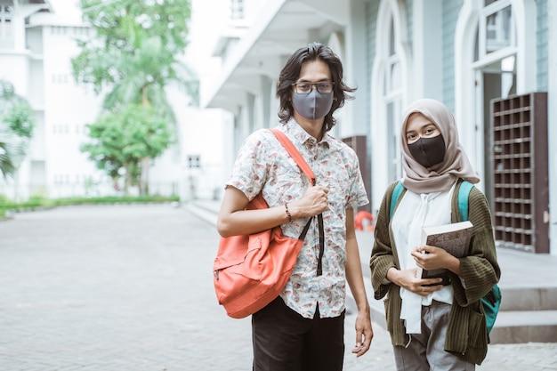 Retrato de alunos usando máscaras, olhando para a frente no pátio do campus.