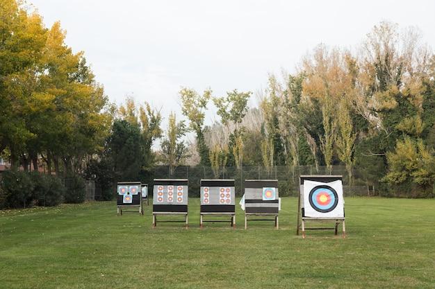 Retrato de alvos de tiro com arco ao ar livre no campo de grama, rodeado por uma floresta.