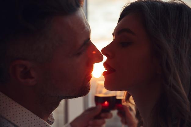 Retrato de amantes se beijando ao pôr do sol e segurando copo com vinho em casa