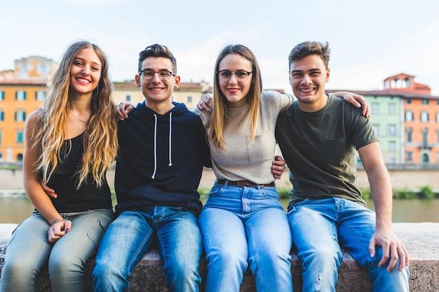 Retrato de amigos adolescentes sentados juntos em uma parede na cidade