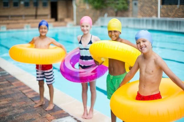 Retrato de amigos carregando argolas infláveis à beira da piscina
