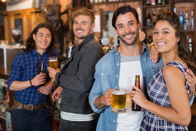 Retrato de amigos com garrafas de cerveja e copos no bar