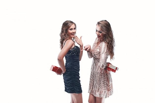 Retrato de amigos de jovens mulheres segurando presentes nas costas indo para trocá-los.