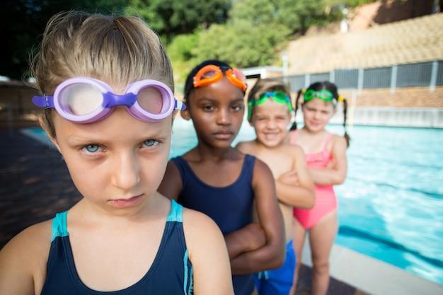 Retrato de amigos em pé à beira da piscina