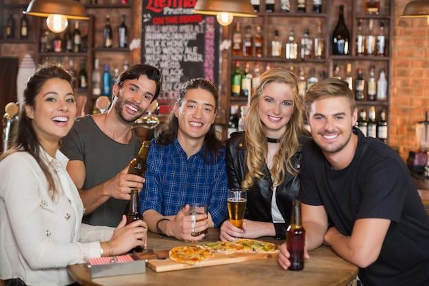 Retrato de amigos felizes comendo pizza com cerveja